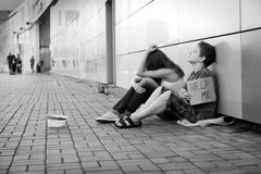 Homelessness. Homeless teenage boy and girl begging in street (The production scene; problem-free children play a role of beggars royalty free stock photo