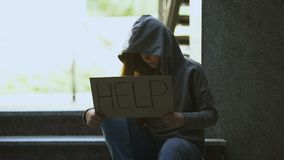 Homeless teenage girl in hoodie showing help sign on stairs, social insecurity