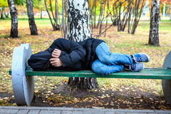 Homeless Teenager. Sleep on the Bench in the Autumn Park Stock Photo