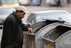 Homeless trash can. Sofia, Bulgaria - March 16, 2015: A homeless man is searching the trash in a trash cans on a busy street in the center of Sofia Royalty Free Stock Photo