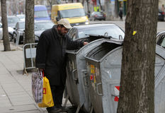 Homeless trash can. Sofia, Bulgaria - March 16, 2015: A homeless man is searching the trash in a trash cans on a busy street in the center of Sofia Stock Images