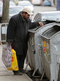 Homeless trash can. Sofia, Bulgaria - March 16, 2015: A homeless man is searching the trash in a trash cans on a busy street in the center of Sofia Royalty Free Stock Photos