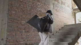 Homeless up stairs with garbage bag behind his back. Sick homeless with garbage bag up stairs in abandoned building. Young bum in dirty torn clothes walks in the stock footage