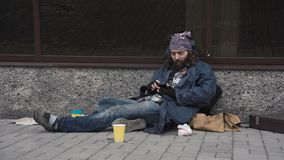 Homeless using smartphone stock footage