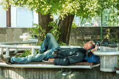 Homeless veteran. Poor hungry and tired homeless man ex military soldier sleep in the shade on the bench in urban city street soci stock images