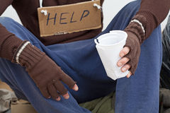Homeless waiting for alms. Homeless with paper cup waiting for the alms on the street royalty free stock photography