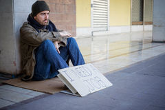 Homeless whit dirty hands drinking alone Stock Images