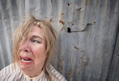 Homeless Woman Crying. Senior homeless woman with too much makeup crying stock photo