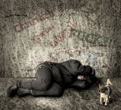 Homeless woman with dog. Lonely, homeless woman with a dog lying on the ground beside a wall covered by grafitti Royalty Free Stock Image