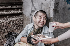 Homeless woman getting help. Homeless poor woman being handed food by volunteer and smiling Royalty Free Stock Image