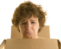 Homeless woman isolated on white. Homeless woman wearing a cardboard box looking depressed Royalty Free Stock Images