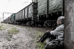 Homeless woman near the rail track. Homeless young woman drinking beer while train passing by royalty free stock image