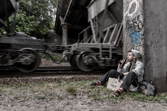 Homeless woman near the rail track. Homeless young woman sitting with sign drinking beer while train passing by royalty free stock photo