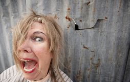 Homeless Woman Screaming. Senior homeless woman with too much makeup screaming Stock Photography