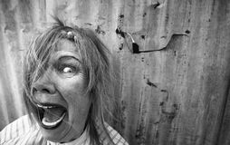Homeless Woman Screaming. Senior homeless woman with too much makeup screaming Royalty Free Stock Photo