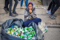 Homeless woman is sitting on the street with a big bag full of beverage cans Stock Images