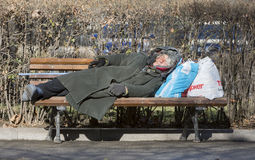 Homeless woman sleeping on a bench Stock Photos