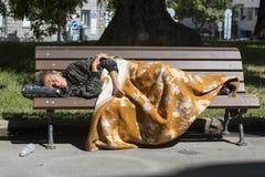 Homeless woman sleeping on a bench Stock Image
