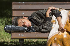 Homeless woman sleeping on a bench Royalty Free Stock Images