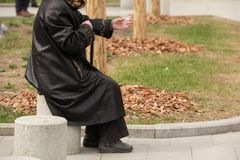 Homeless woman on the street begging with a plastic Cup in her hand. Homeless woman on the street begging with a plastic Cup in his hand sitting on a stone royalty free stock images