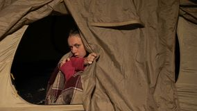 Homeless woman in tent looking out, trembling from cold at night, shelter. Stock footage stock video footage