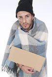Homeless wrapped in his blanket begging with a sign Stock Photo