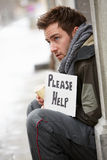 Homeless Young Man Begging In Street. Holding up sign Stock Image