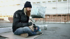 Homeless young man in dirty clothes drink alcohol sitting near shopping cart on the street at cold winter day stock video footage