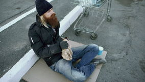 Homeless young man in dirty clothes drink alcohol sitting near shopping cart on the street at cold winter day stock footage