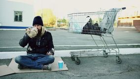 Homeless young man in dirty clothes drink alcohol sitting near shopping cart on the street at cold winter day. Homeless young man in dirty clothes drink alcohol Stock Photos