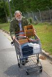 Homelessness. Homeless Vietnam veteran pushes a shopping cart containing his possessions down the side of the street Royalty Free Stock Photo