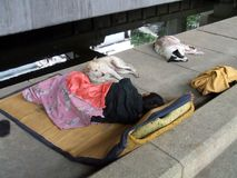 Homelessness. Asian man and pets or dogs sleeping in the street Stock Images