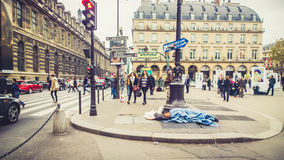 Homelessness in Paris. Homeless man in Paris laying on the ground (Louvre Museum in Paris France Royalty Free Stock Image
