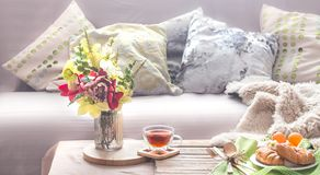 Homely cozy spring interior in the living room. With a vase and flowers homemade breakfast, home comfort concept royalty free stock photo