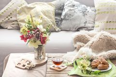 Homely cozy spring interior in the living room. With a vase and flowers homemade breakfast, home comfort concept stock photography