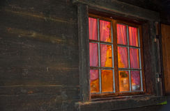 Homely vibe behind the window with glazing bars of a log cabin Royalty Free Stock Images