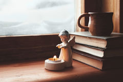 Homely wnter concept of window sill. Warm and comfy winter concept. Book, cup of tea and candlestick on wooden window sill in old house. Reading and relaxing in royalty free stock photo