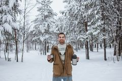 Homem à moda alegre com uma garrafa térmica do chá quente em uma floresta do pinho fotografia de stock royalty free
