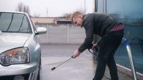 Homem à moda atrativo novo que lava o seu sportcar de prata com o jato de água no carwash do autosserviço É com cuidado video estoque