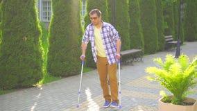Homem à moda com um ferimento em muletas que anda no parque em um dia ensolarado filme