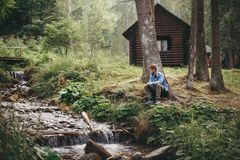 Homem à moda do moderno que senta-se e que relaxa na cabine de madeira na frente imagem de stock