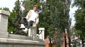 Homem à moda do ruivo que relaxa no parque verão filme