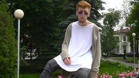 Homem à moda do ruivo que relaxa no parque verão video estoque