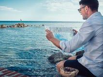 Homem à moda, guardando um mapa do turista em suas mãos imagens de stock