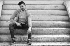 Homem à moda na camiseta com a barba que senta-se em escadas Fotografia de Stock Royalty Free