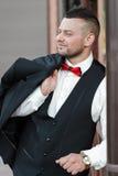 Homem à moda novo em um terno Retrato do noivo O noivo está guardando seu revestimento em seu ombro, vista lateral fotografia de stock royalty free