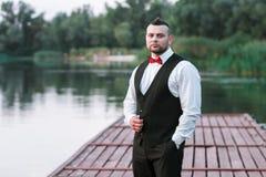 Homem à moda novo em um waistcoat, em um retrato horizontal do noivo, em um retrato em um fundo da natureza, no rio e no cais fotografia de stock royalty free