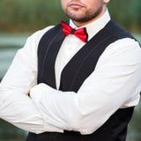 Homem à moda novo em um waistcoat, em um retrato vertical do noivo, em um retrato em um fundo da natureza, no rio e no cais fotos de stock royalty free