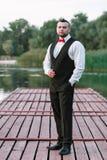 Homem à moda novo em um waistcoat, em um retrato vertical do noivo, em um retrato em um fundo da natureza, no rio e no cais fotos de stock