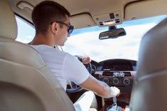 Homem à moda novo nos óculos de sol que conduzem um carro Vista da parte traseira, com o assento do passageiro traseiro fotos de stock